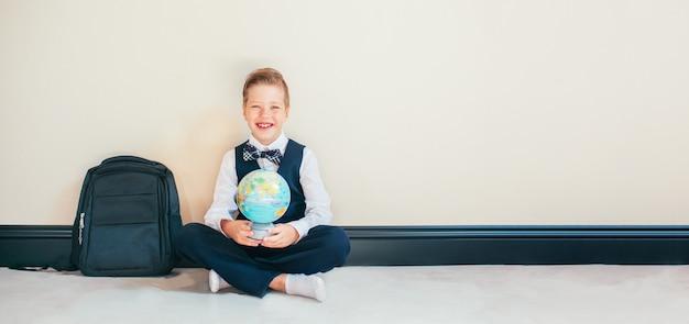 Loiro menino sorridente vestida de uniforme escolar, sentada no chão com um globo e olha para a câmera. conceito de educação e viagens. copyspace