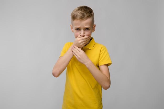 Loiro menino triste caucasiano em camiseta amarela, fechando a boca com as mãos em cinza