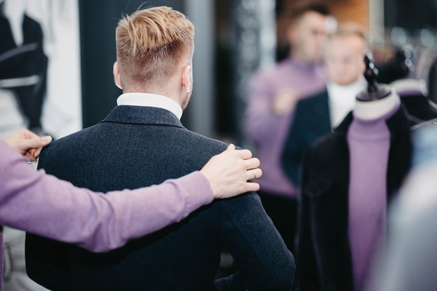 Loiro milenar em um traje de negócios escolhe roupas em uma loja o homem está fazendo compras