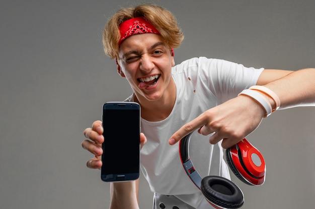 Loiro mostra uma tela de telefone com uma maquete e fones de ouvido em uma parede cinza