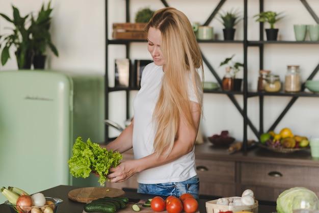 Loiro, mulher jovem, ficar, em, cozinha, segurando, alface