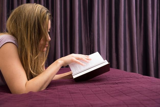 Loiro, mulher jovem, mentindo, cama, livro leitura