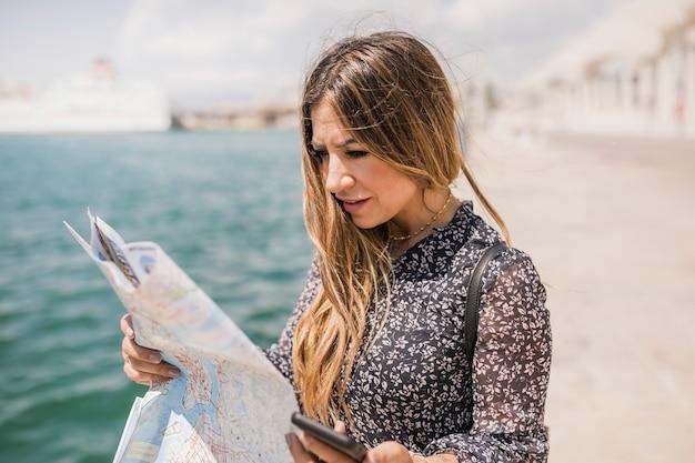 Loiro, mulher jovem, olhar, mapa, para, direção, segurando, telefone pilha