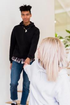 Loiro, mulher jovem, segurando, dela, namorado, mão, olhando câmera