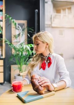 Loiro, mulher jovem, sentando, em, a, caf�, segurando, pão, e, vidro suco