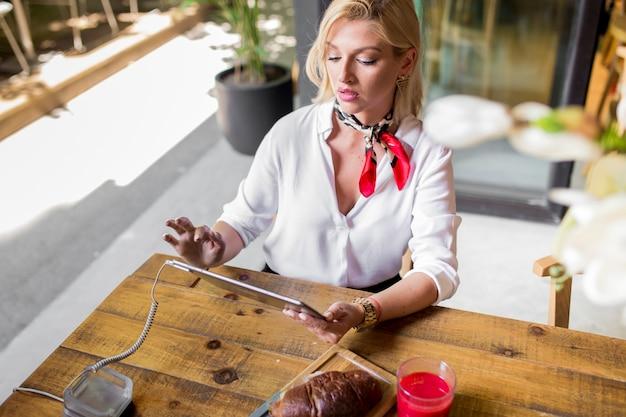 Loiro, mulher jovem, usando, tablete digital, em, restaurante