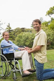 Loiro, mulher sorri, em, cadeira rodas, com, sócio, ajoelhando, ao lado, dela