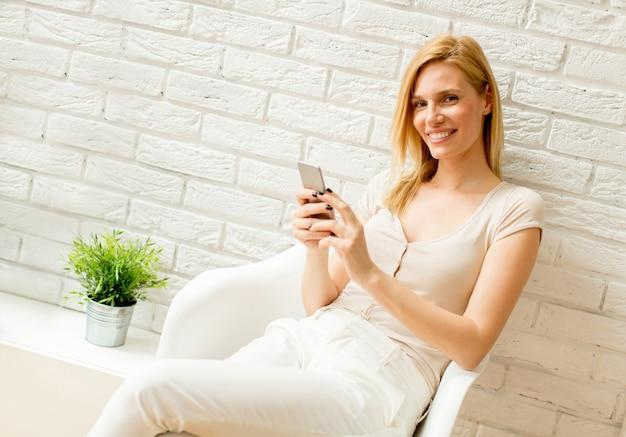 Loiro, mulher, usando, telefone móvel, em, a, sala