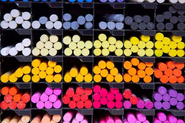 Loja de arte em crayons pastel multicoloridos em celas de madeira