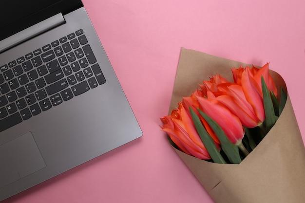 Loja de flores online. laptop e buquê de tulipas em fundo rosa pastel.