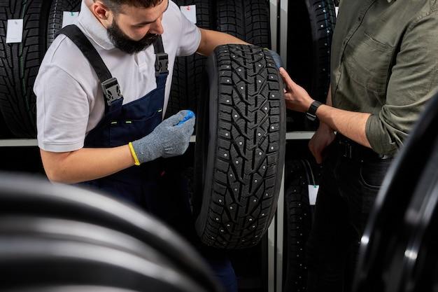 Loja de garagem do proprietário segurando o melhor pneu em um shopping de supermercado, medindo a roda de borracha do carro. no local de trabalho