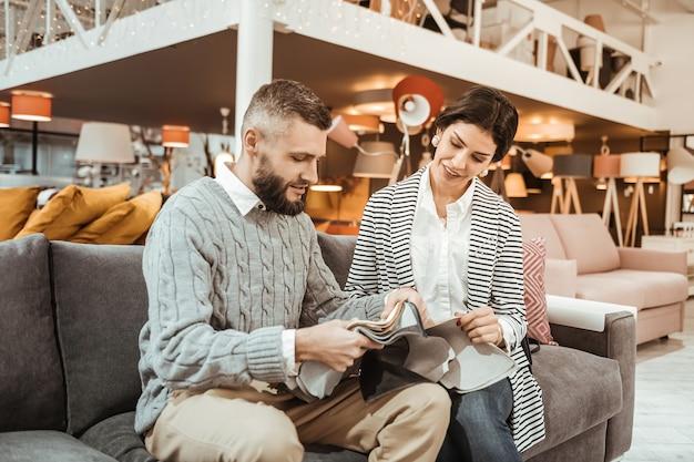 Loja de móveis. casal bonito e interessado observando peças de tecido enquanto está sentado no sofá cinza