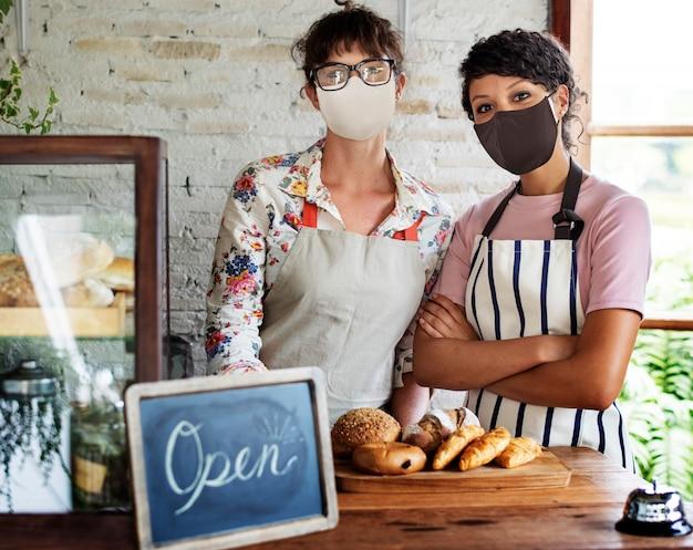 Loja de padaria aberta após pandemia cobiçosa nova equipe normal com máscaras faciais