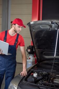 Loja de reparação de carros. jovem sério barbudo de macacão com laptop aberto em pé perto do carro atento olhando sob o capô