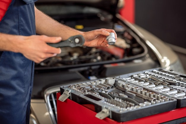 Loja de reparação de carros. mãos masculinas com chave e detalhe perto da caixa aberta com peças sobressalentes e capô do carro