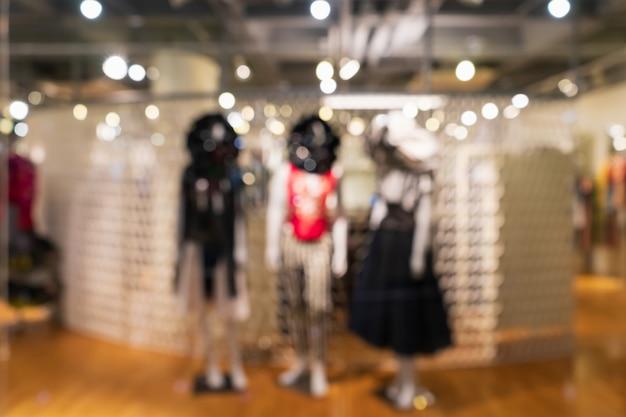 Loja de roupa moderna obscura abstrata da forma em um shopping para o fundo, conceito da compra da roupa.