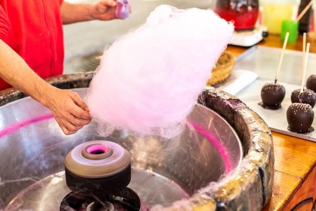 Lojista preparando uma nuvem de algodão doce em uma feira para algumas crianças.