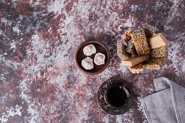 Lokum e biscoitos de gergelim com um copo de chá, vista de cima