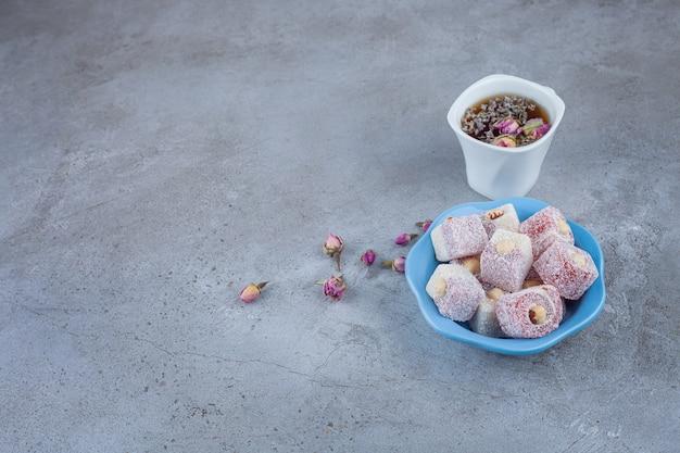 Lokum turco com avelãs e uma xícara de chá de ervas.