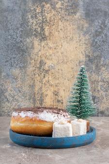 Lokums, donut e uma estatueta de árvore em uma bandeja azul no mármore.