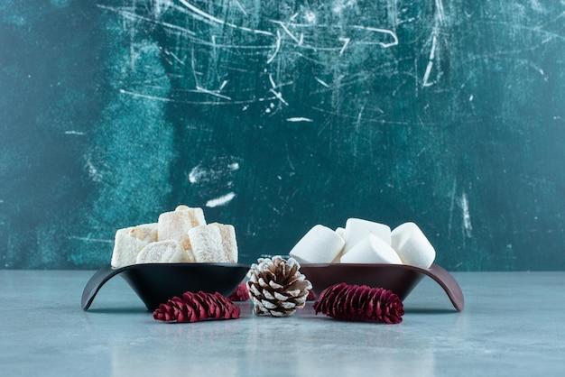 Lokums e marshmallows em pequenas tigelas ao lado de pinhas no mármore.