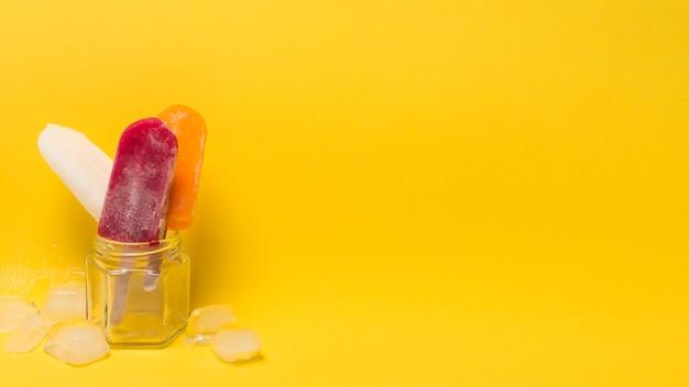 Lolly de gelo colorido em jarra perto de gelo