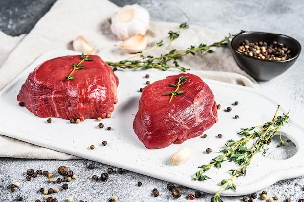 Lombinho de carne em mármore. bife de mignon de filé cru em uma tábua branca. fundo cinza. vista do topo