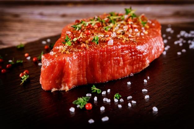Lombinho de carne fresca com ervas e sal sobre a placa de pedra preta.