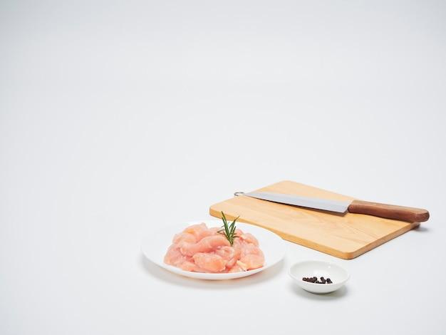Lombinho de frango fresco com placa de madeira, faca.