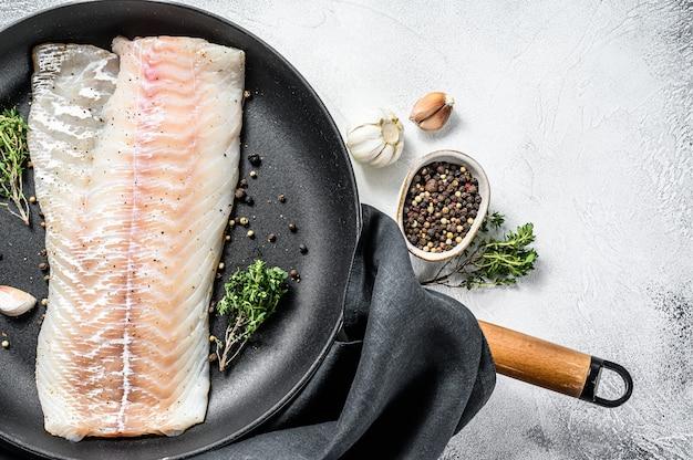 Lombo de bacalhau cru com ervas em uma frigideira. fundo cinza. vista do topo. copie o espaço