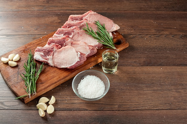 Lombo de bife fresco de carne crua e especiarias e uma faca encontra-se na madeira., plana leigos