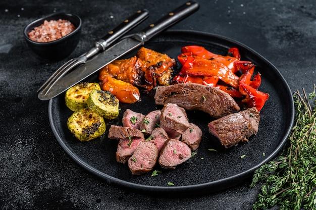 Lombo de cabra ou cordeiro assado bife de carne no prato com legumes grelhados. fundo de madeira preto. vista do topo.