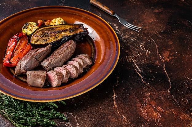 Lombo de carneiro grelhado filé de carne, lombo de cordeiro no prato rústico com legumes. fundo escuro. vista do topo. copie o espaço.