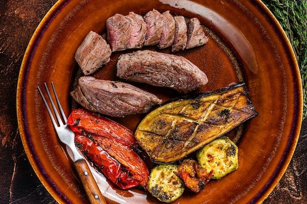 Lombo de carneiro grelhado filé de carne, lombo de cordeiro no prato rústico com legumes. fundo escuro. vista do topo.