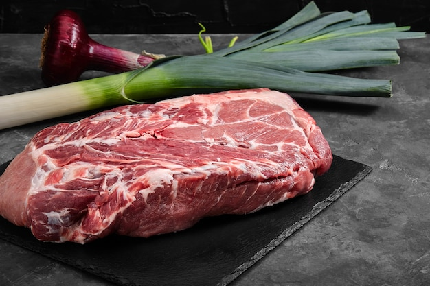 Lombo de porco, carne fresca em um prato de ardósia em uma superfície cinza com vegetais