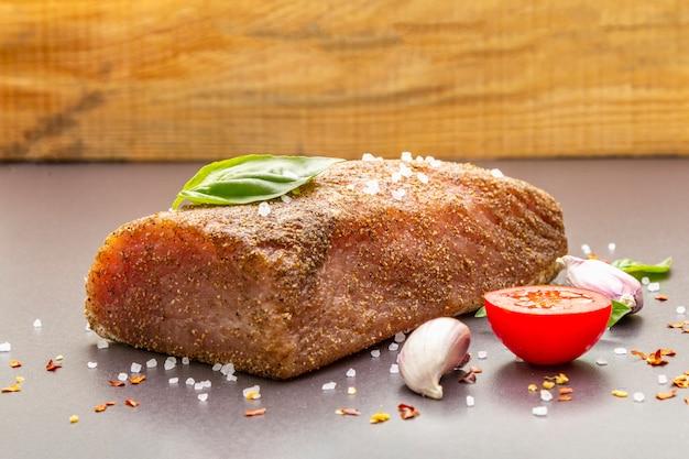 Lombo de porco cru com legumes, espécies e ervas