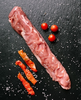 Lombo de porco cru no prato de ardósia com pimentão e tomate