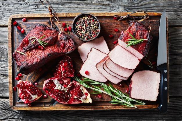 Lombo de porco defumado e vitrificado cortado em uma tábua de madeira rústica com sementes frescas de granada, grãos de pimenta e faca, visão horizontal de cima, flatlay, close-up