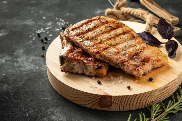 Lombo de porco grelhado em uma placa de madeira em uma superfície escura,