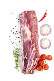 Lombo de vaca. um grande pedaço de carne com legumes e ervas frescas em fundo branco. vista do topo.
