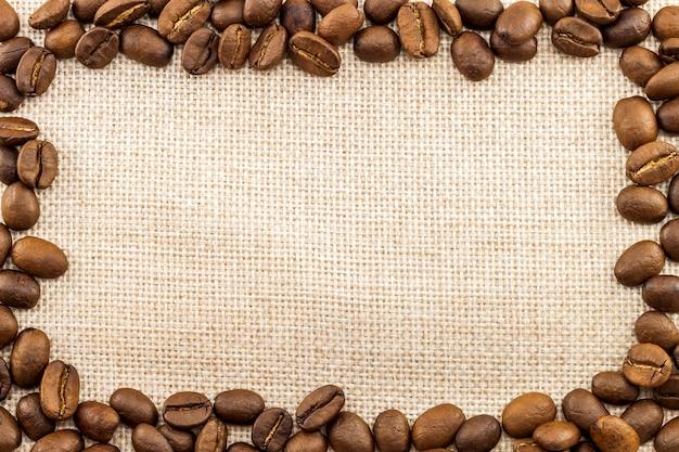 Lona de pano de saco de serapilheira e feijões de café colocados circularmente no fundo da foto do círculo. copie o espaço. fronteira do café