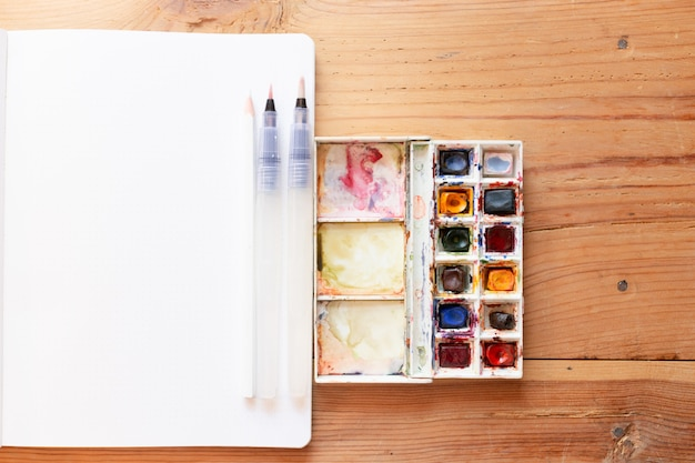 Lona de tinta aquarela e pincéis usados para criar novas pinturas. iniciando um diário com marcadores em um bloco de notas. novos começos. arte e criatividade conceito de fundo