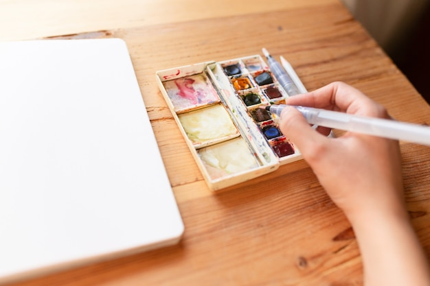 Lona de tinta aquarela e pincéis usados para criar novas pinturas. mão segurando um pincel. iniciando um diário com marcadores em um bloco de notas. novos começos. conceito de arte e criatividade.