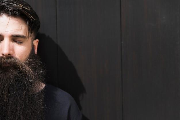 Long barbudo jovem com o olho fechado contra a parede preta