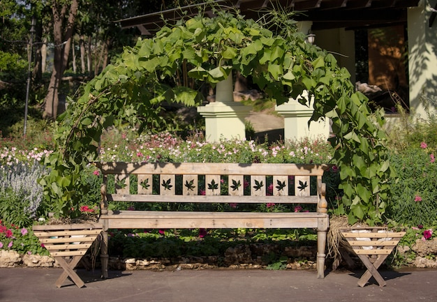 Long cadeira de madeira no jardim ao lado da passarela