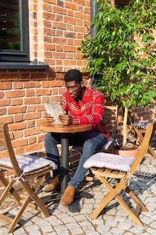 Long shot de homem estiloso lendo