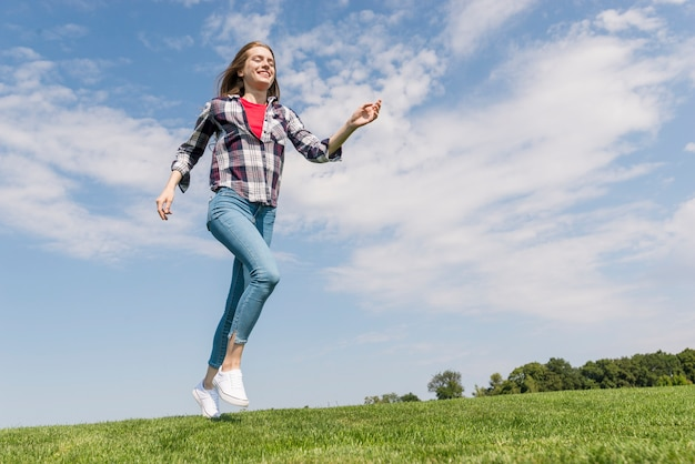 Long shot garota alegre correndo na grama