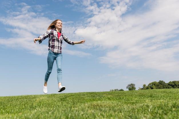 Long shot garota feliz correndo na grama