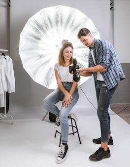 Long shot homem e mulher no estúdio de fotografia profissional