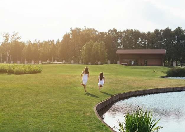 Long shot mãe e filha correndo ao ar livre